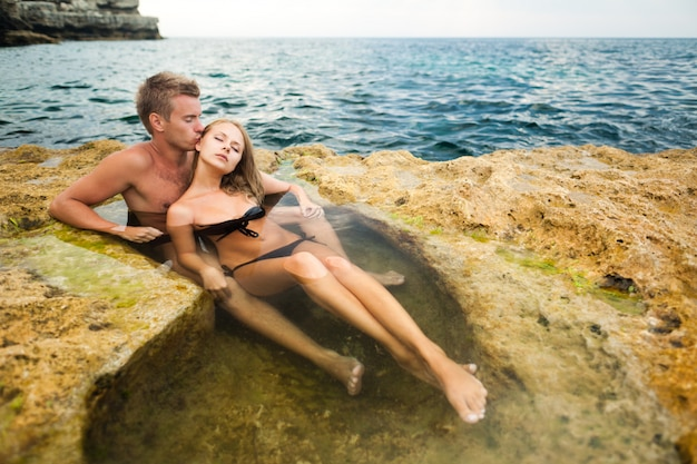 Young happy beautiful couple woman and man enjoying time in natural rock pool with water with rocks