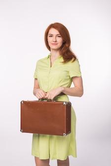 白い背景の上のスーツケースを保持している若い幸せな美しい生姜の女性