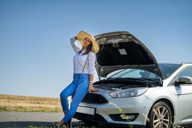 Молодая счастливая красивая модель возле своей машины в летней поездке