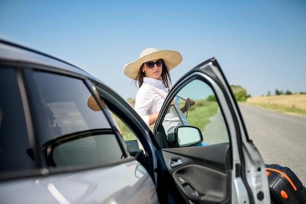 夏の旅行で彼女の車の近くの若い幸せな美しいモデル