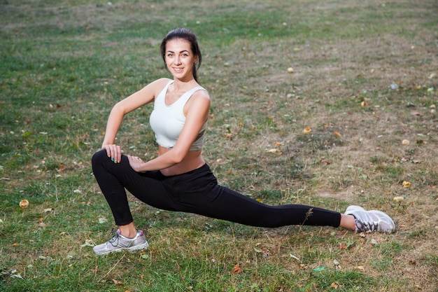 젊은 행복 한 아름 다운 섹시 한 여자는 공원 정원에서 스트레칭입니다. 사람들 배경입니다. 검은 머리에 검은색과 흰색의 운동복과 행복과 미소를 지닌. 여름이나 가을 시즌에.