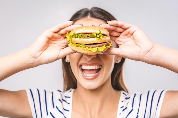 ハンバーガーを食べる若い幸せな美しい女性
