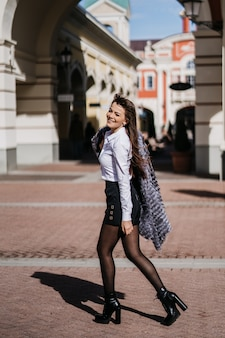 街を歩いて毛皮のコート、白いスカート、黒いシャツの若い幸せな美しい女性。