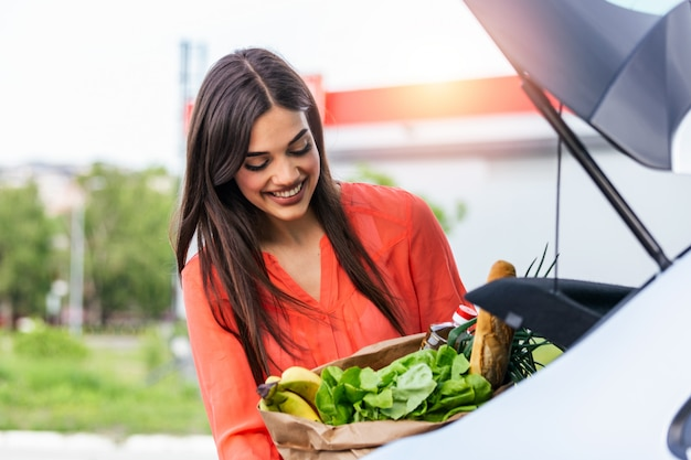 Young happy beautiful woman shifts the purchase from shopping cart in the trunk of a car on the parking