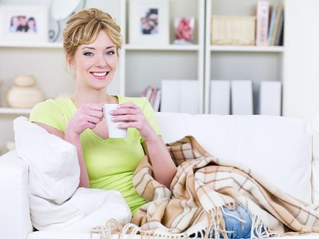 Молодая счастливая красивая женщина с чашкой согревающего напитка дома