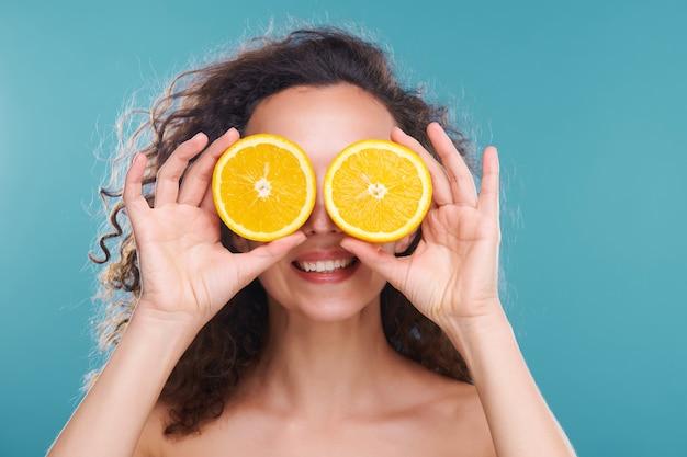 孤立した顔の世話をしながら彼女の目でジューシーなオレンジの半分を保持している暗い巻き毛の若い幸せな美しい女性