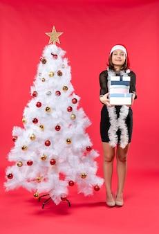 サンタクロースの帽子と贈り物を保持している装飾されたクリスマスツリーの近くに立っている若い幸せな美しい女性