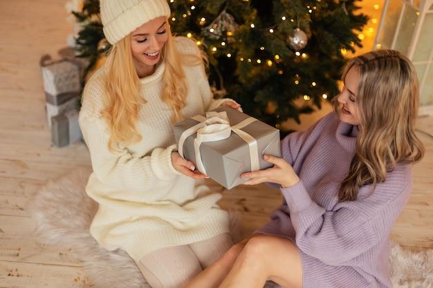 セーターと帽子をかぶったファッショナブルなニットの服を着た笑顔の若い幸せな美しい女性は、クリスマスツリーの近くで贈り物をして床に座ります。冬休み