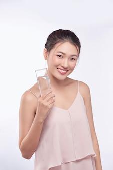笑顔でガラスの水を保持している若い幸せな美しさの健康なアジアの女性