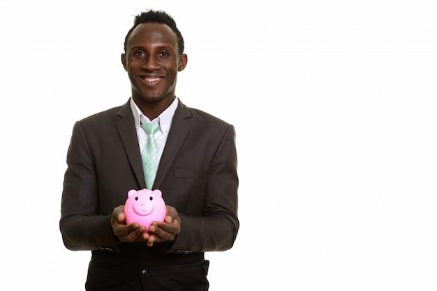 笑顔と貯金箱を保持している若い幸せな黒アフリカの実業家