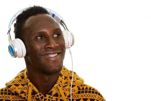 若い幸せなアフリカ黒人男性笑顔と音楽を聴く