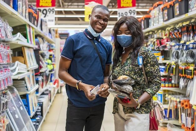 Giovani coppie nere felici con le mascherine sanitarie che comperano in un negozio di alimentari