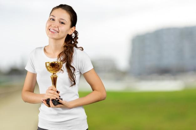 チャンピオンカップを保持している若い幸せな黒人女性