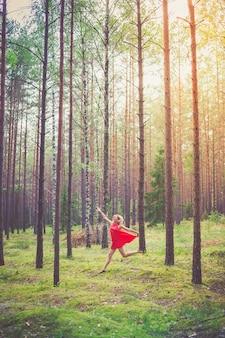 소나무 숲에서 춤추는 빨간 드레스를 입은 젊은 행복한 금발 여성