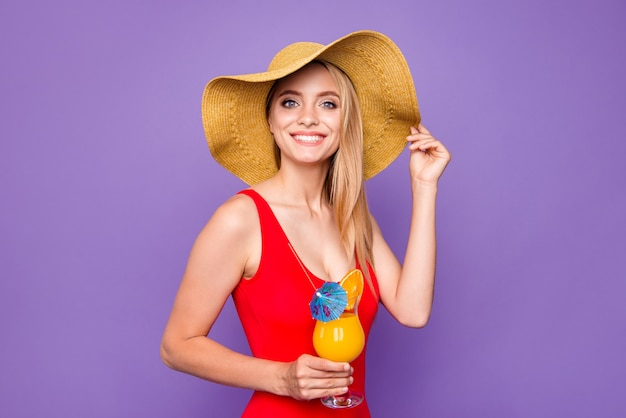 Young happy blonde girl holding cold summer cocktail in hand isolated on purple