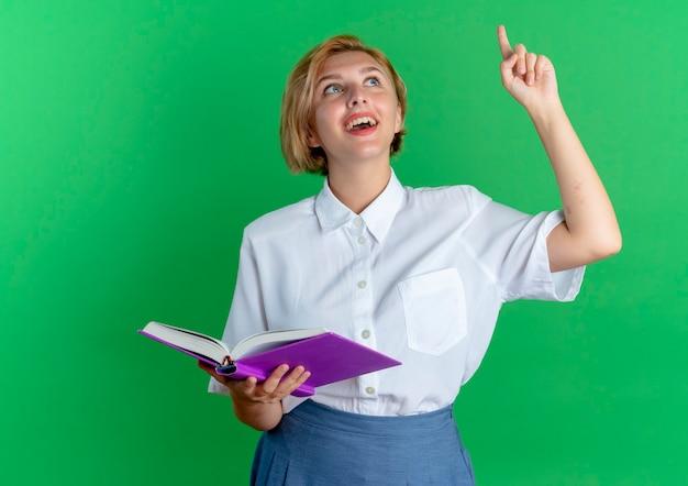 La giovane ragazza russa bionda felice tiene il libro che osserva e che indica in su isolato su fondo verde con lo spazio della copia