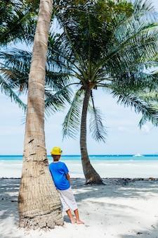 야자수가 있는 하얀 모래 열대 해변에서 즐거운 어린 행복한 소년