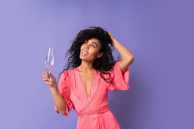 Giovane donna brasiliana felice con capelli ricci in abito elegante rosa in posa con un bicchiere di champagne sopra la parete viola. atmosfera di festa.
