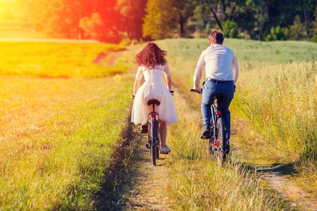 若い幸せな新郎新婦が牧草地で自転車に乗ってカメラに戻る