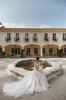 夏の日に豪華な別荘の中庭にある噴水のそばに座っている豪華なウェディング ドレスを着た若い幸せな花嫁