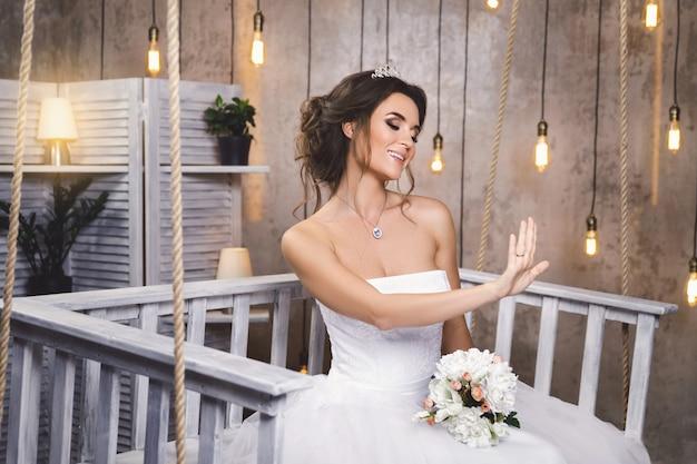 電球の多い部屋で美しい緑豊かなドレスを着ている若い幸せな花嫁