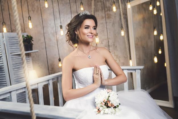 Молодая счастливая невеста носить красивое пышное платье в комнате с большим количеством лампочек