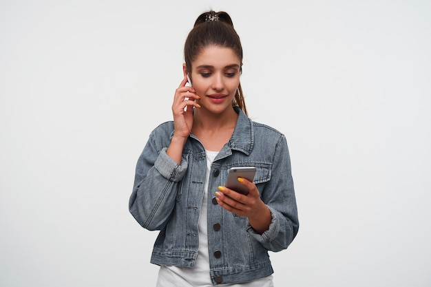 Young happy brunette lady wears in white t-shirt and denim jackets, holds smartphone and broadly smiles, listening new song of favorite band in new headphones.