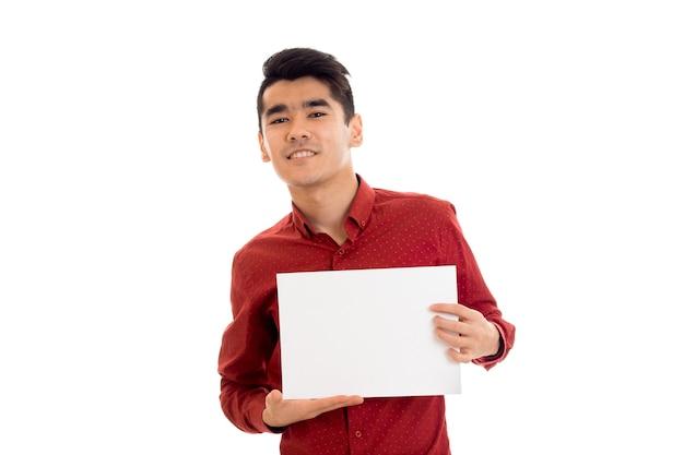 Молодой счастливый брюнет в красной футболке позирует с белым плакатом на стене