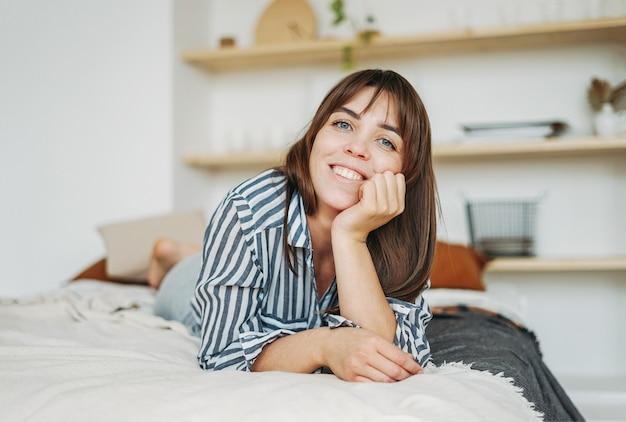 Молодая счастливая брюнетка женщина в повседневной одежде отдыхает на кровати в ярком интерьере