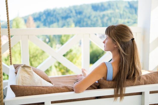 따뜻한 여름날을 즐기는 부드러운 베개와 함께 테라스 소파에 누워 젊은 행복 한 갈색 머리 여자. 신선한 공기에 자유 시간의 개념입니다.