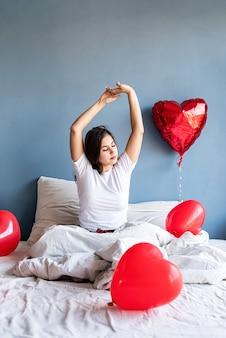 Молодая счастливая брюнетка женщина сидит без сна в постели с красными воздушными шарами в форме сердца