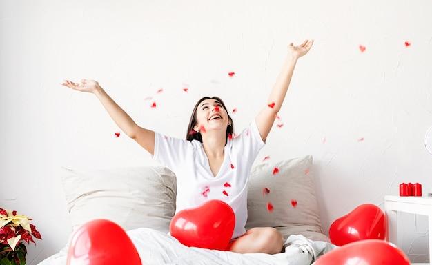 공기에 색종이를 던지고 붉은 심장 모양의 풍선과 함께 침대에 앉아 젊은 행복 갈색 머리 여자