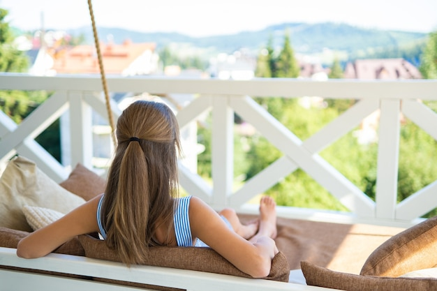 暖かい夏の日を楽しんでいる柔らかいクッションとテラスのソファに座っている若い幸せなブルネットの女性。新鮮な空気の自由時間の概念。