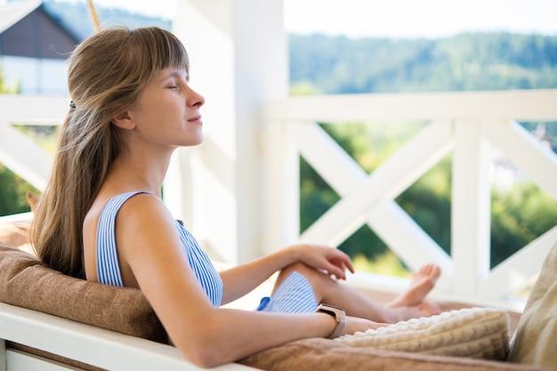 따뜻한 여름날을 즐기는 부드러운 쿠션이 있는 테라스 소파에 앉아 있는 젊은 행복한 브루네트 여성.