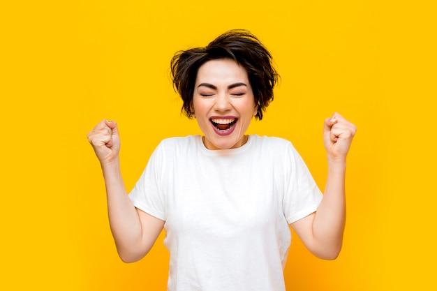 黄色の背景に白いtシャツに短い髪の若い幸せなブルネットの女性。黄色の背景にさまざまな感情を持つ若い女性の肖像画。テキストのためのスペース