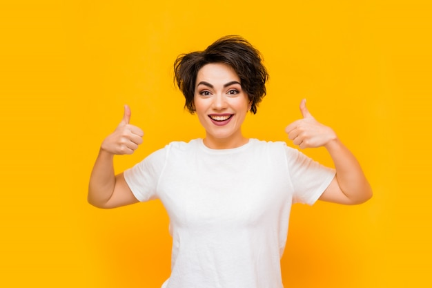 Young happy brunette woman with a short haircut in a white t-shirt on a yellow background. portrait of a young woman with various emotions on a yellow background. space for text