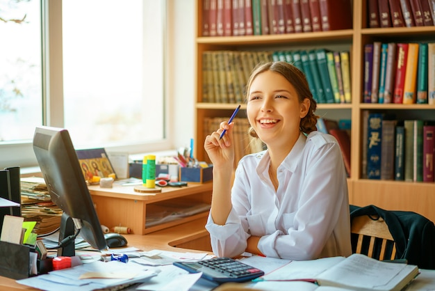 Young happy business lady in white shirt sitting at table with computer and papers working environment.