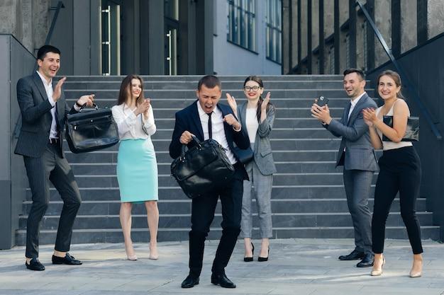 事務所ビルからスーツとネクタイダンスを着ている若い幸せなビジネスマネージャー。同僚は応援しています。現代のオフィスからの多様でやる気のあるビジネス人々。