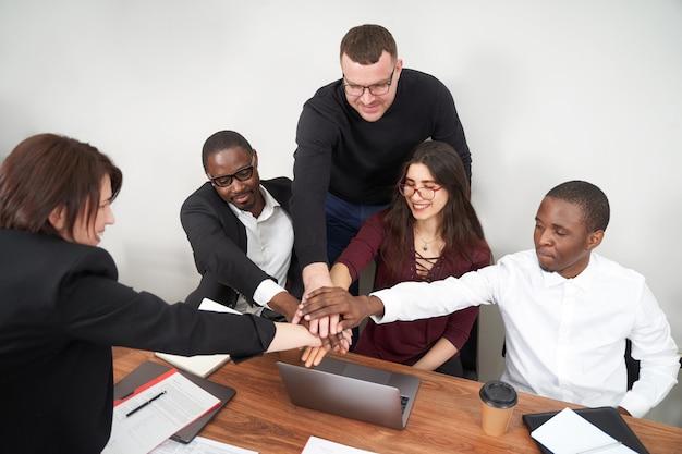 近代的なオフィス、多民族のチームワークで一緒に働く若い幸せなビジネス人々。会議で手を重ねるビジネスパートナー