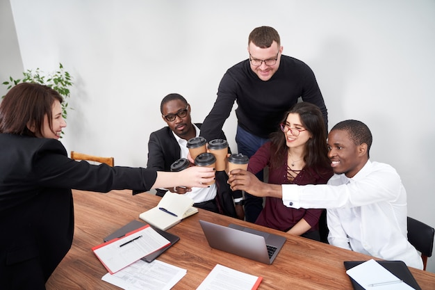 Young happy business people working together in modern office, multiethnic teamwork. toasting with coffee cups
