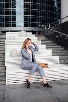 Молодая счастливая бизнес-леди разговаривает по телефону на фоне офисного здания.
