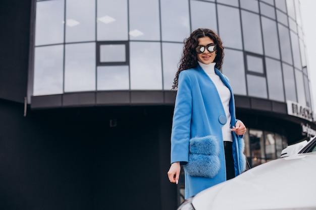 Giovane donna d'affari felice che esce dalla sua auto