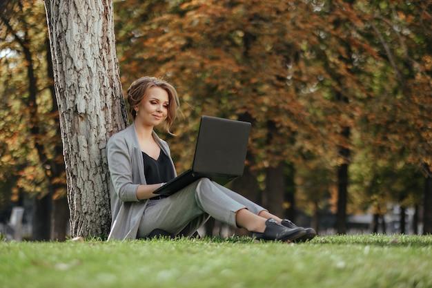 ラップトップを持つ若い幸せなビジネス女性