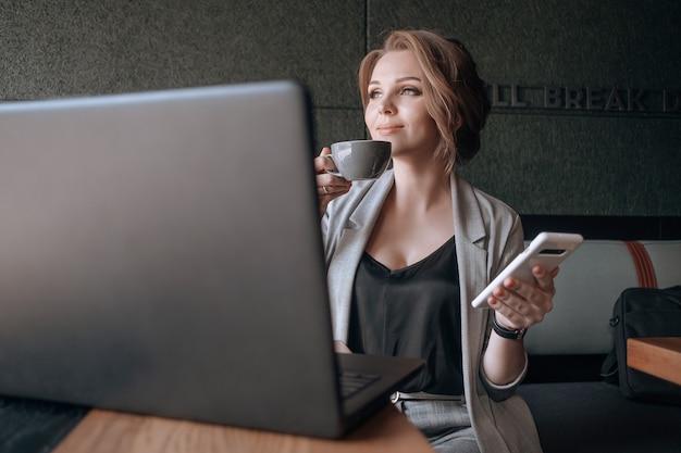 ラップトップを持つ若い幸せなビジネス女性 Premium写真