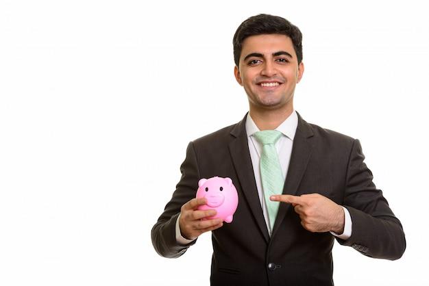 貯金箱を押しながら指している若い幸せなビジネスマン