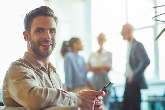 Молодой счастливый бизнесмен, сидя в современном офисе, держа смартфон и улыбаясь в камеру в то время как
