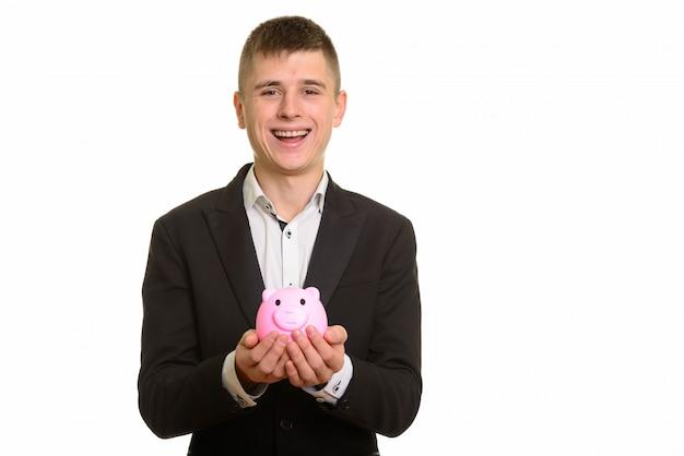 笑顔で貯金箱を保持している若い幸せなビジネスマン