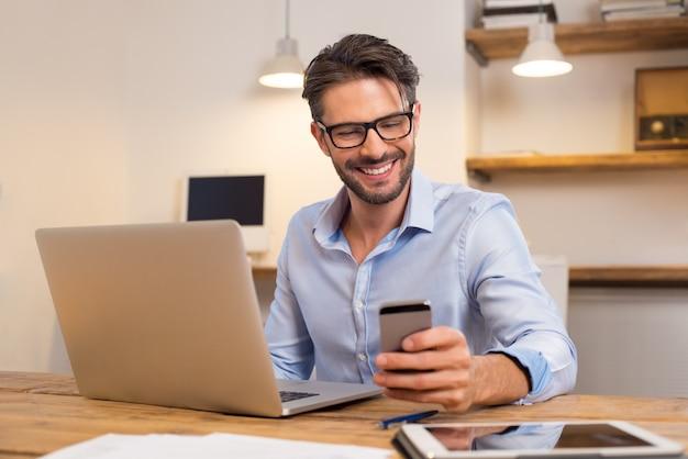 그의 스마트 폰 읽는 동안 웃 고 젊은 행복 한 사업가. 사무실에서 스마트 폰으로 메시지를 읽고 웃는 사업가의 초상화. 사무실에서 그의 책상에서 일하는 남자.