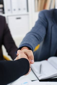 Young happy businessmen have meeting in office shake hands with each other