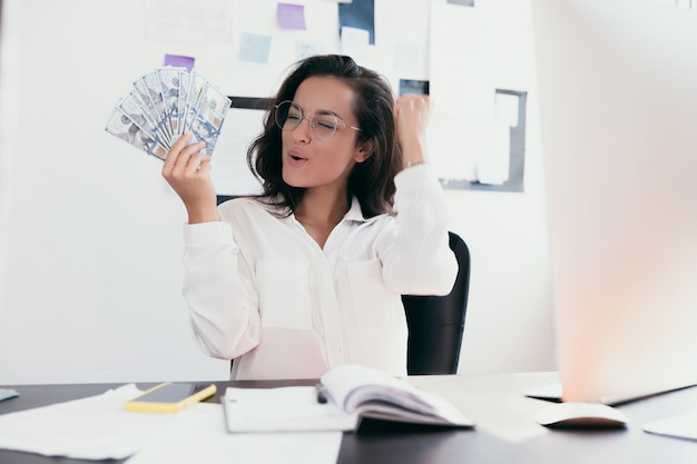 Young happy businesswoman holding bills of dollars
